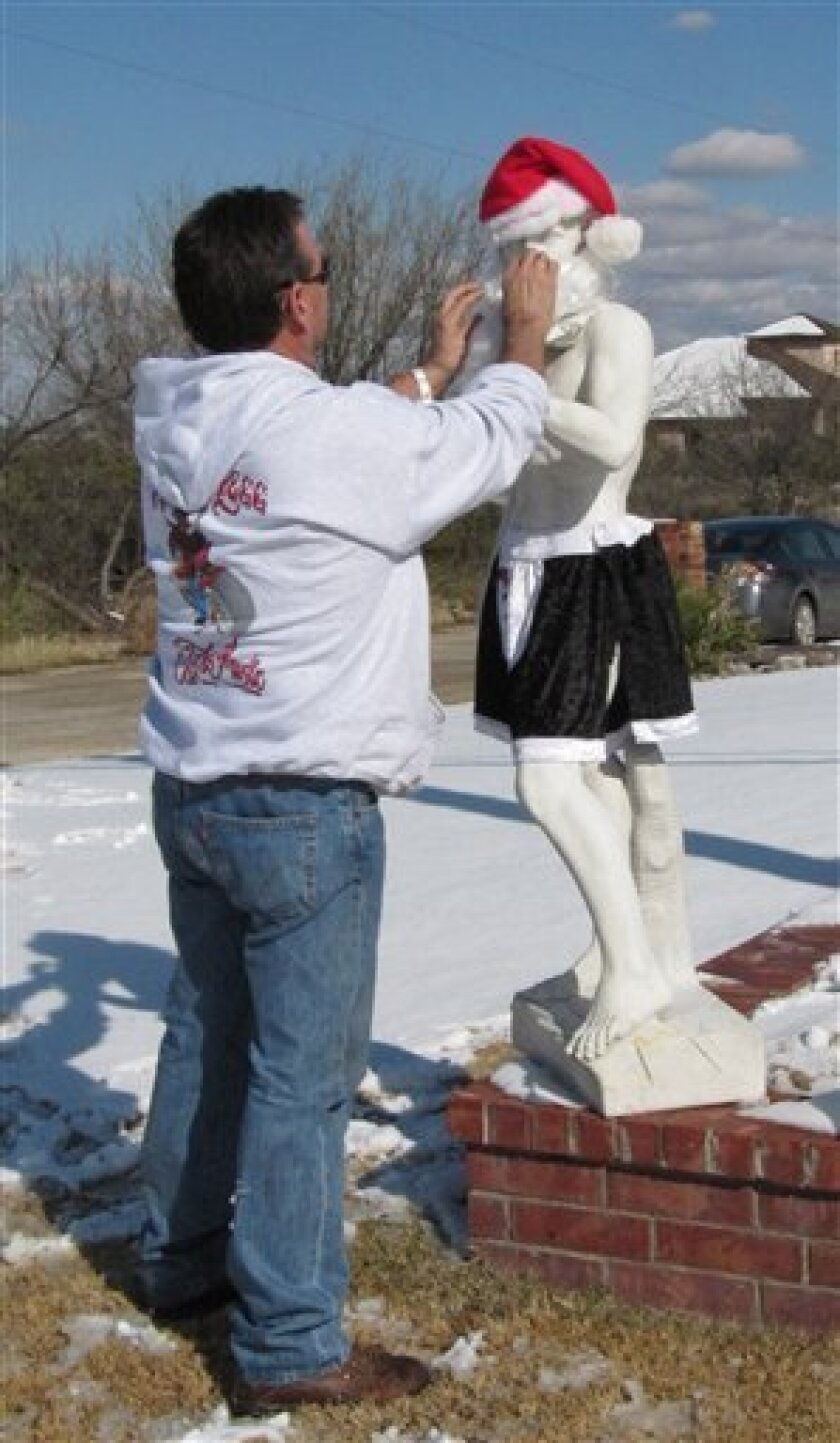 This Friday, Dec. 4, 2009 photo shows Barry McBee adjusting a Santa beard on a statue of Michelangelo's David in front of a home in Big Spring, Texas. McBee, put his statue of Michelangelo's David in his front yard with only a Santa cap and beard, but neighbors and parents complained to town officials that their kids were asking why Santa was naked. The homeowner relented and put a pair of shorts on the replica of the famous statue. (AP Photo/Betsy Blaney)