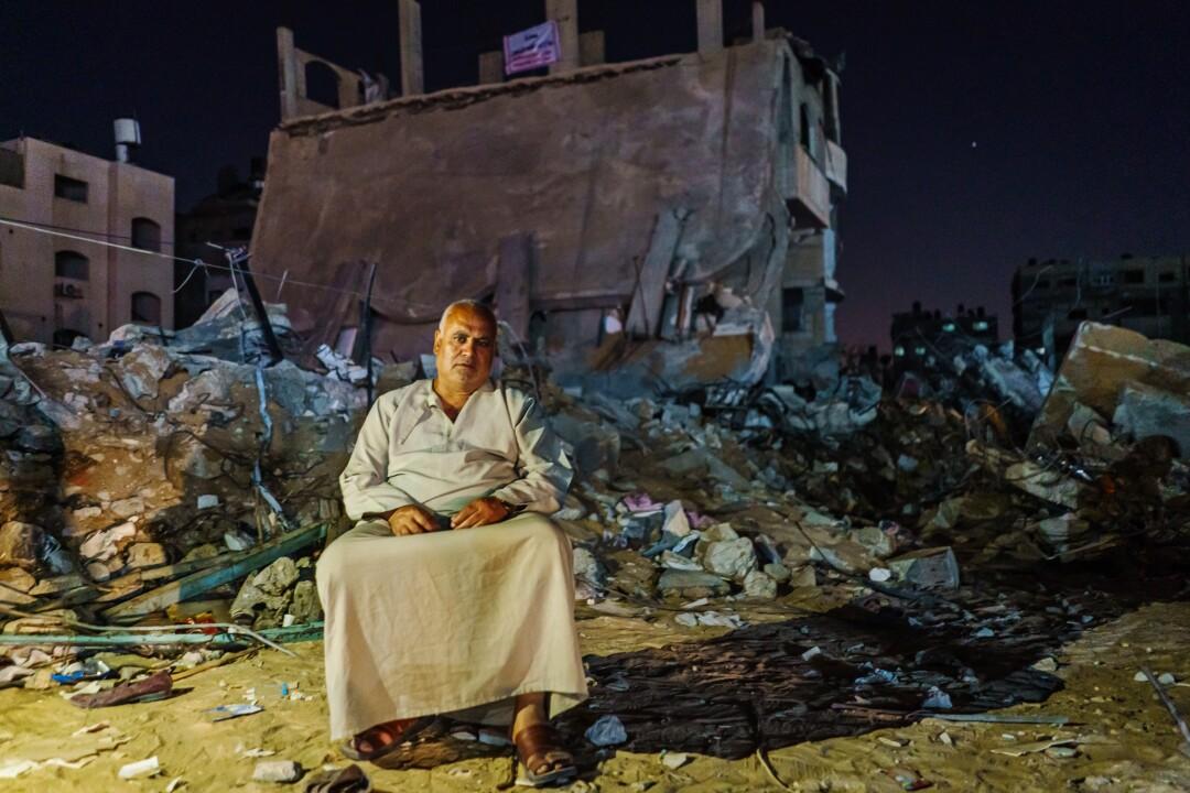 رباح المدحون در مقابل بقایای ساختمان خود در شهر غزه نشسته است.