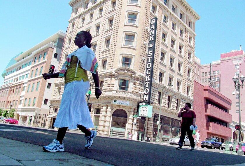 Pedestrians cross a street in Stockton.