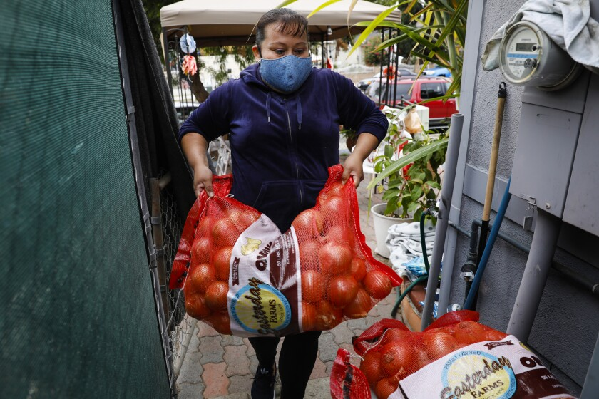 Araceli Mora, who volunteers at a free food stand, stores supplies next to a Sherman Heights home.