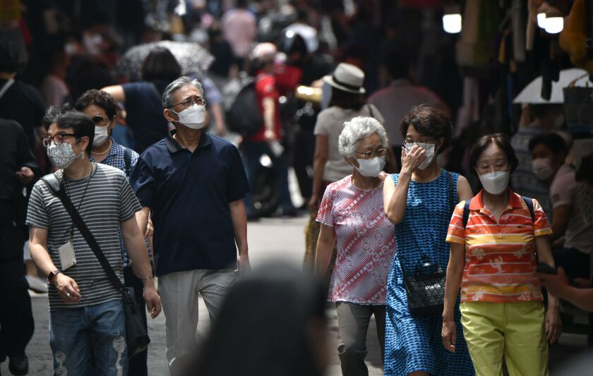 Pedestrians wearing masks walk through a market in Seoul.
