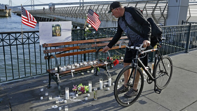 Craig Warner of Palo Alto, Calif., leaves a bell at a memorial site for Kathryn Steinle on Pier 14 in San Francisco on Friday.
