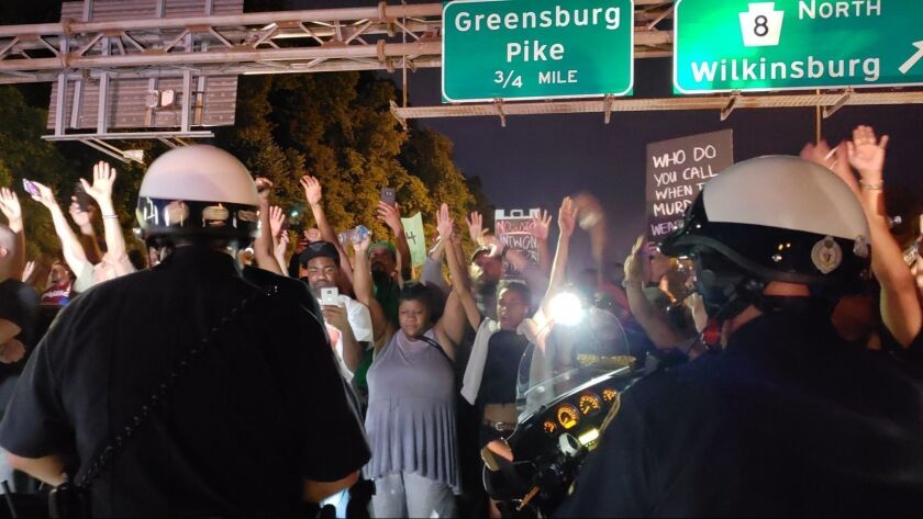 """Protesters chant """"Hands up! Don't shoot!"""" at officers during a protest on Interstate 376 near Pittsburgh on June 21."""