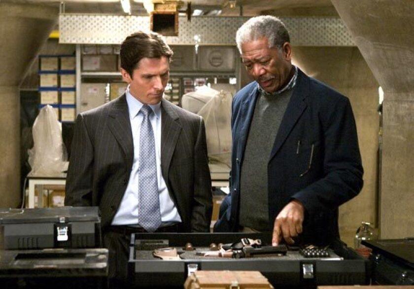 "Christian Bale and Morgan Freeman in the film ""Batman Begins."""