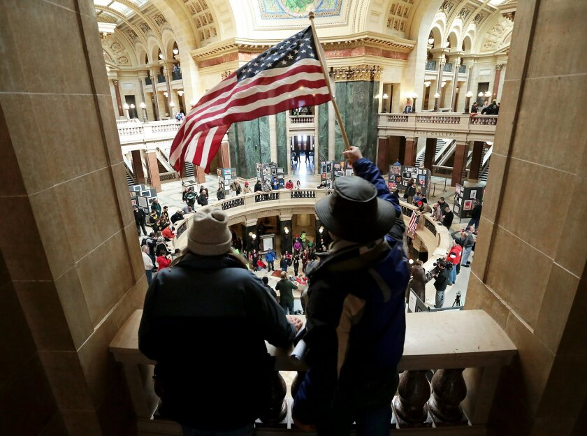 Dave Mandehr, left, and Andy Olsen join demonstrators in the rotunda of the Wisconsin State Capitol in Madison, Wis. as rallies against proposed right-to-work legislation continue, Tuesday, Feb. 24, 2015. (AP Photo/Wisconsin State Journal, John Hart)