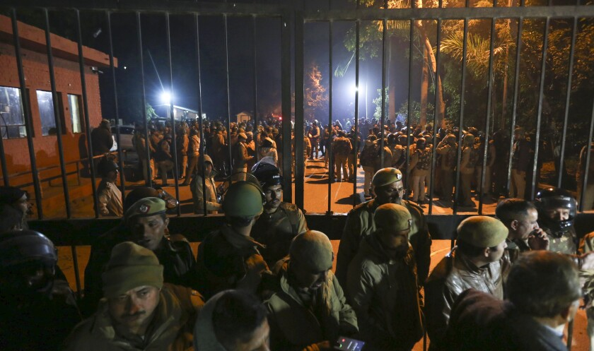 Police arrive at Jawaharlal Nehru University in New Delhi late Sunday after masked assailants beat students and teachers with sticks, injuring more than 30.
