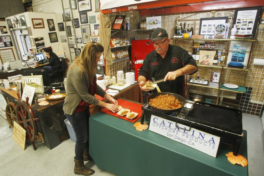 Tommy Gomes makes fish tacos for employee Rebecca Gardon during lunch time at Catalina Offshore Products.