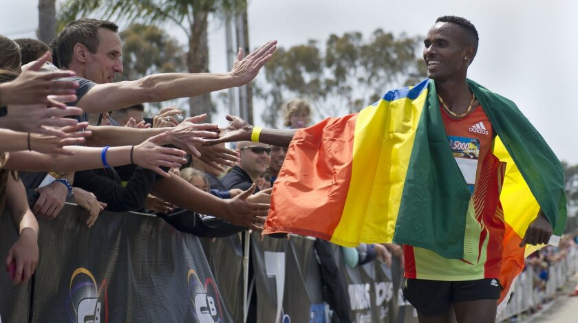 Dejen Gebremeskel, of Ethiopia, celebrates with the crowd after winning his third consecutive Elite Men segment of the Carlsbad 5000.