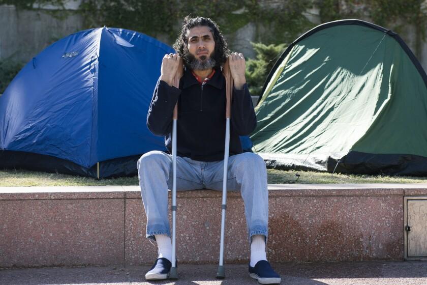 ARCHIVO. En esta foto del 5 de mayo de 2015, el ex detenido de Guantánamo Abu Wa'el Dhiab, de Siria, aparece sentado frente a la embajada de EEUU en una manifestación para exigir ayuda financiera en Montevideo, Uruguay. (Foto AP / Matilde Campodonico)