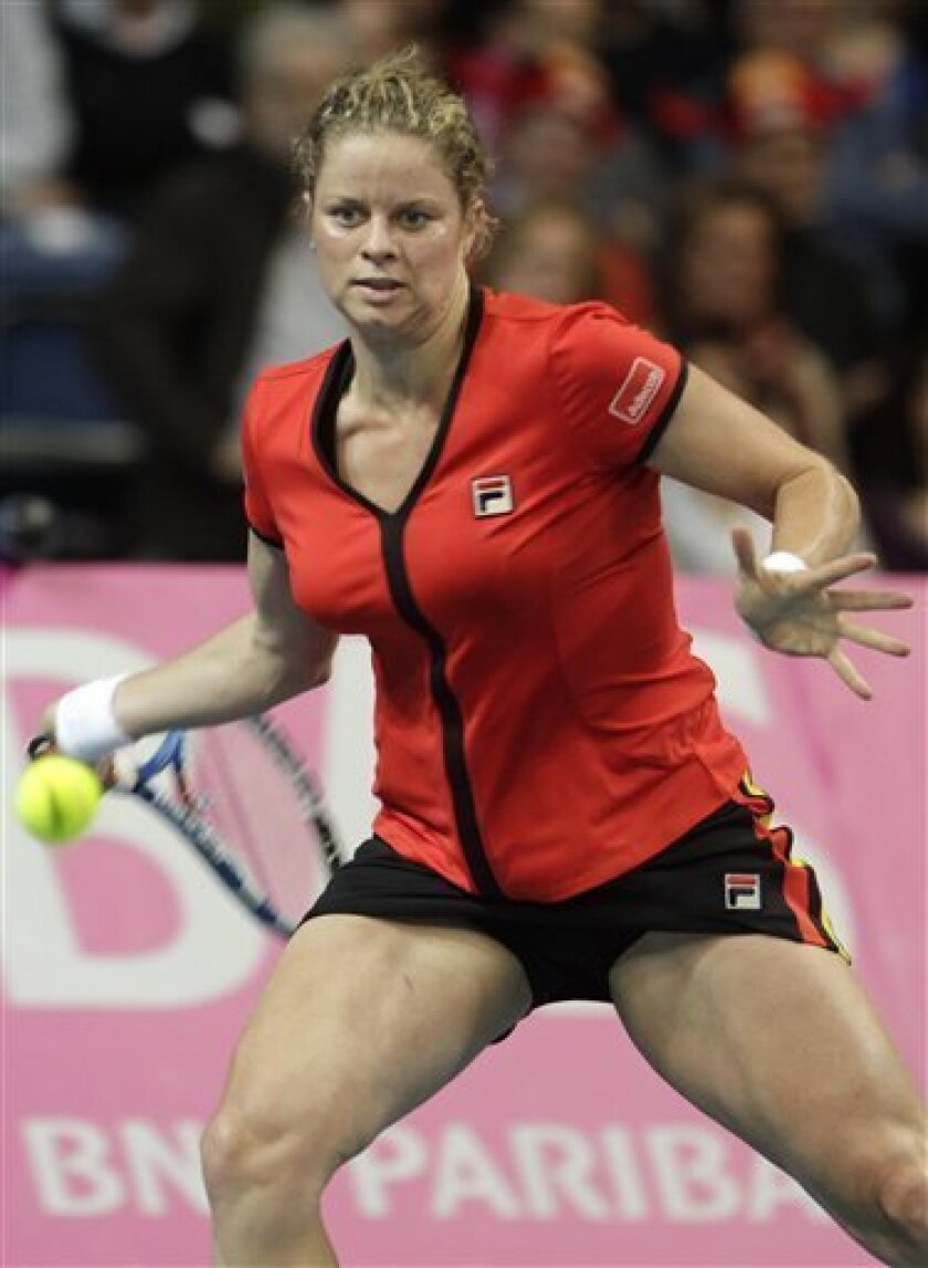 Belgium's Kim Clijsters returns the ball towards US player Melanie Oudin during the World Group Fed Cup match in Antwerp, Belgium, Saturday, Feb. 5, 2011. Belgium leads on the first day 2-0. (AP Photo/Yves Logghe)