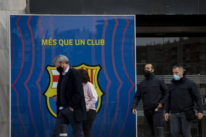 Catalan police walk outside FC Barcelona's offices in Barcelona, Spain, Monday March 1, 2021. Spanish police detained several people after raiding Barcelona's stadium in a search and seize operation related to an investigation into club officials. Police say detentions were made but do not say who or how many people were taken into custody. (AP Photo/Joan Monfort)
