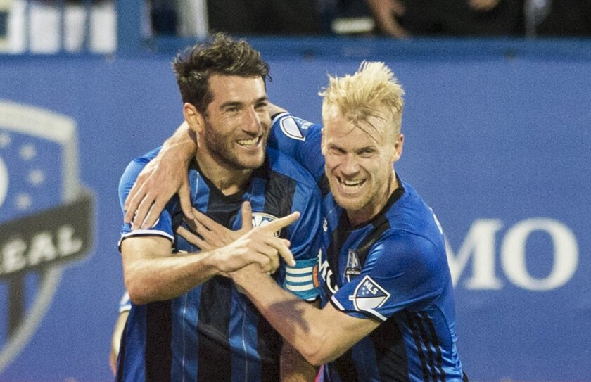 Montreal Impact's Ignacio Piatti, left, celebrates with teammate Kyle Bekker after scoring against the Los Angeles Galaxy during first-half MLS soccer game action in Montreal, Saturday, May 28, 2016. (Graham Hughes/The Canadian Press via AP) MANDATORY CREDIT