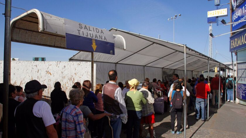 People wait in line to be inspected by U.S. border patrol officers to enter from Mexico to the U.S., at the San Ysidro point of entry, in Tijuana