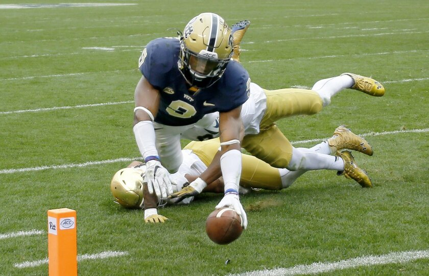 Pittsburgh running back Jordan Whitehead (9) dives for the end zone and a touchdown past Notre Dame linebackers James Onwualu (17), bottom, Jaylon Smith (9) in the third quarter of an NCAA football game, Saturday, Nov. 7, 2015 in Pittsburgh. Notre Dame won 42-30. (AP Photo/Keith Srakocic)