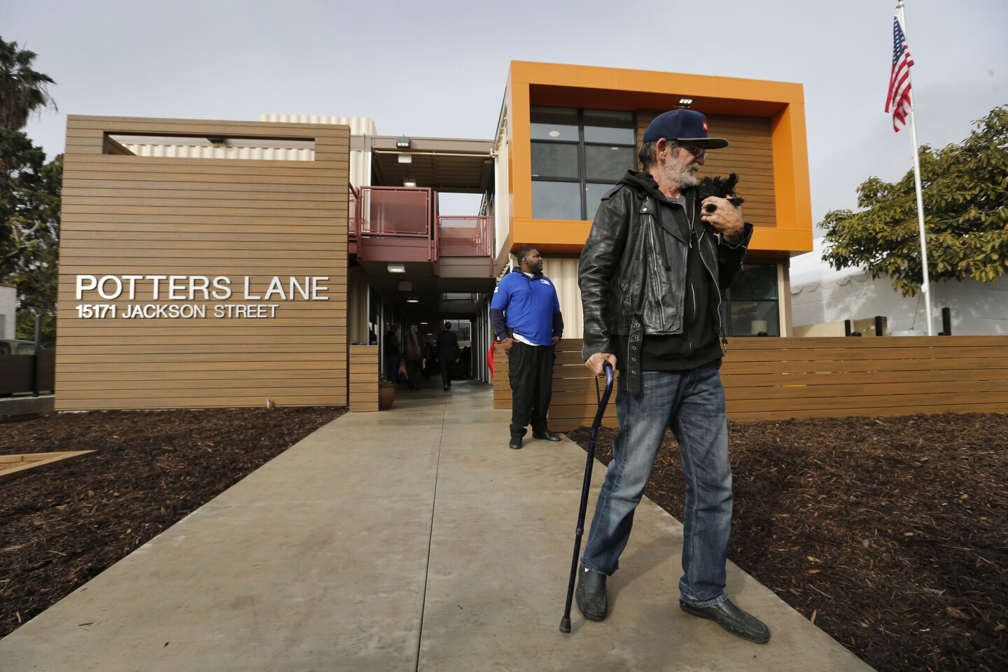 Homeless Army veteran Jimmy Palmiter, 59, holds his dog Fifi while touring his future home during the dedication of Potter's Lane, the state's first multifamily housing development built with recycled shipping containers.