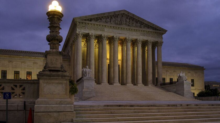 In this Oct. 5, 2018 photo the U. S. Supreme Court building stands quietly before dawn in Washington. The Supreme Court won't let the Trump administration begin enforcing a ban on asylum for any immigrants who illegally cross the U.S.-Mexico border. New Justice Brett Kavanaugh and three other conservative justices sided with the administration. The court's order Friday leaves in place lower court rulings that blocked President Donald Trump's proclamation in November automatically denying asylum to people who enter the country from Mexico without going through official border crossings. (AP Photo/J. David Ake)