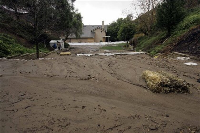 A mud slide covers the street in front of a home along San Antonio road in Yorba Linda, Calif., Monday, Dec 15, 2008. A powerful pre-winter storm slammed California with rain and snow on Monday, snarling roads, triggering two traffic fatalities, collapsing the roof of an occupational school and forcing hundreds of people to flee homes in a suburb at risk of mudslides after a devastating wildfire last month. (AP Photo)