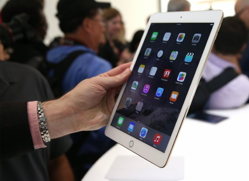 An attendee looks at an iPad Air 2 during an Apple event in Cupertino, Calif.