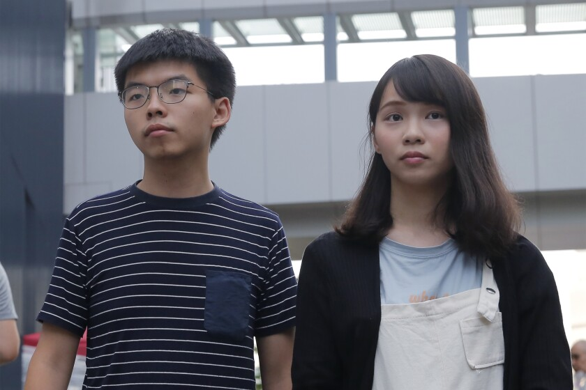 Pro-democracy activists Joshua Wong and Agnes Chow meet media outside a government office in Hong Kong in June