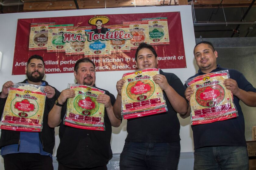 En sus manos sostienen los diferentes sabores de tortillas. Aparecen de izquierda a derecha: Anthony, Tony y Ronald Alcázar; y Gabriel Gutiérrez, gerente de la fábrica Mr. Tortilla.