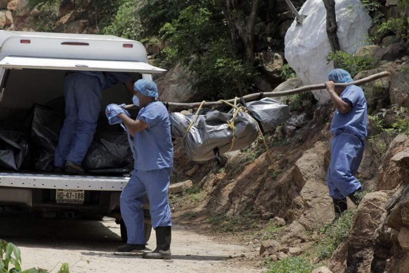 Forenses trasladan un cuerpo hasta una camioneta luego de hallar al menos 10 cadáveres en tumbas clandestinas a las afueras del centro vacacional de Acapulco. (Foto AP/Bernandino Hernandez)