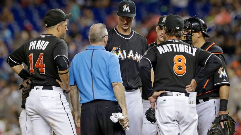 The Marlins' Colin Rea, third from left, talks manager Don Mattingly (8) in the fourth inning of a game against the St. Louis Cardinals on Saturday, July 30, 2016, in Miami. Rea was relieved by David Phelps. Rea had an elbow injury in his Miami debut.