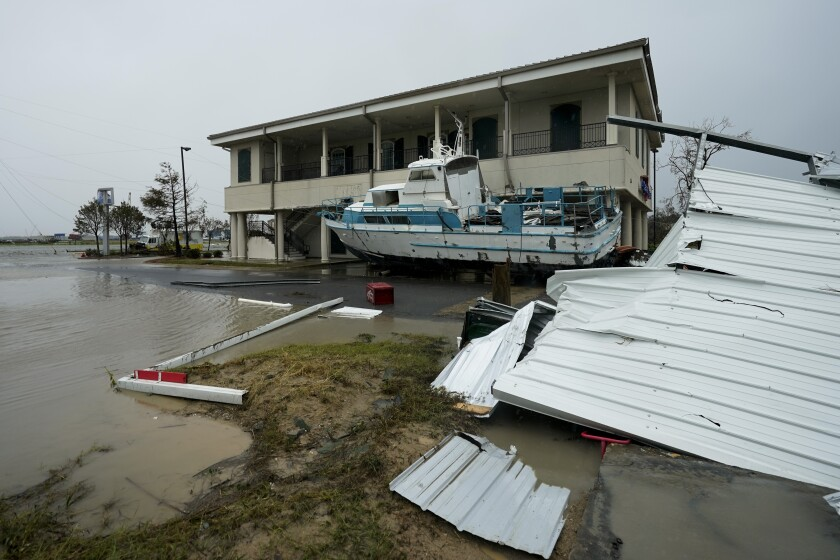 Flooding surrounds a damaged building and boat Friday in Cameron, La.