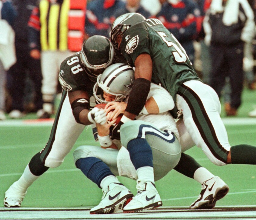 Cowboys quarterback Troy Aikman suffered a concussion on this 1997 play when sacked by the Eagles' Jimmie Jones, left, and William Thomas.