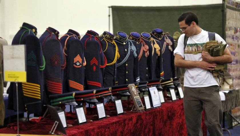 Collector Matthew Caffrey of Yorba Linda, walks by a display of old uniforms at the American Society of Military Insignia Collectors show. photo by  Nancee E. Lewis / Nancee  Lewis Photography