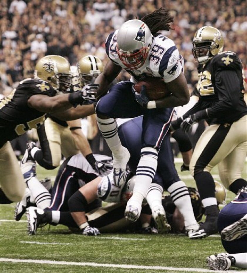 New England Patriots Laurence Maroney (39) runs past New Orleans Saints Marvin Mitchell, left, to score a two-yard touchdown during the third quarter of an NFL football game, Monday, Nov. 30, 2009, in New Orleans. (AP Photo/Patrick Semansky)