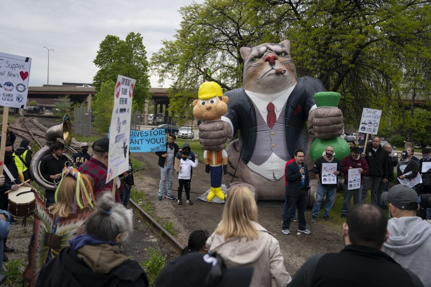 """A man speaks to a small crowd outdoors while standing in front of a balloon depicting a """"fat cat."""""""