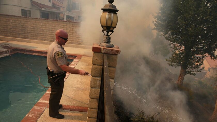 L.A. County Sheriff's Deputy Jason Viger hoses down a hot spot as fire threatens a home in Newhall.