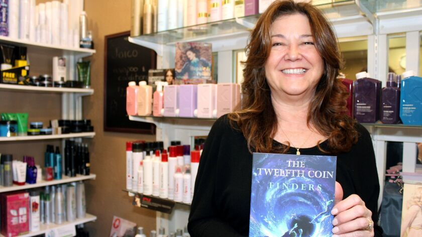 A proud Kimberly Erjavac and her new book upstage her salon's hair product display in Toluca Lake.