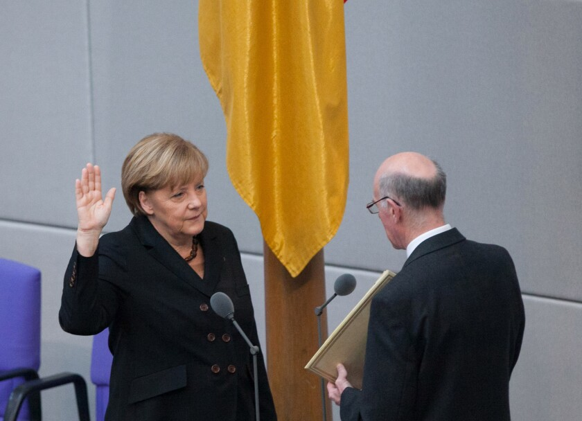 German Chancellor Angela Merkel takes the oath of office as a new coalition government is sworn in Tuesday in Berlin.