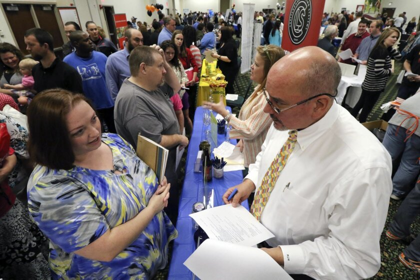 Frances Scoggins, left, speaks to Michael McCall, general manager for Chattanooga Labeling Systems, about her resume during a huge 15-county North Georgia job fair at The Colonnade in Ringgold, Ga., on Thursday, April 2, 2015. Scoggins has been unemployed for the past 4-months and is looking for a safety or manufacturing job. The U.S. government issues the March jobs report on Friday, April 3, 2015. (AP Photo/Chattanooga Times Free Press, Dan Henry)