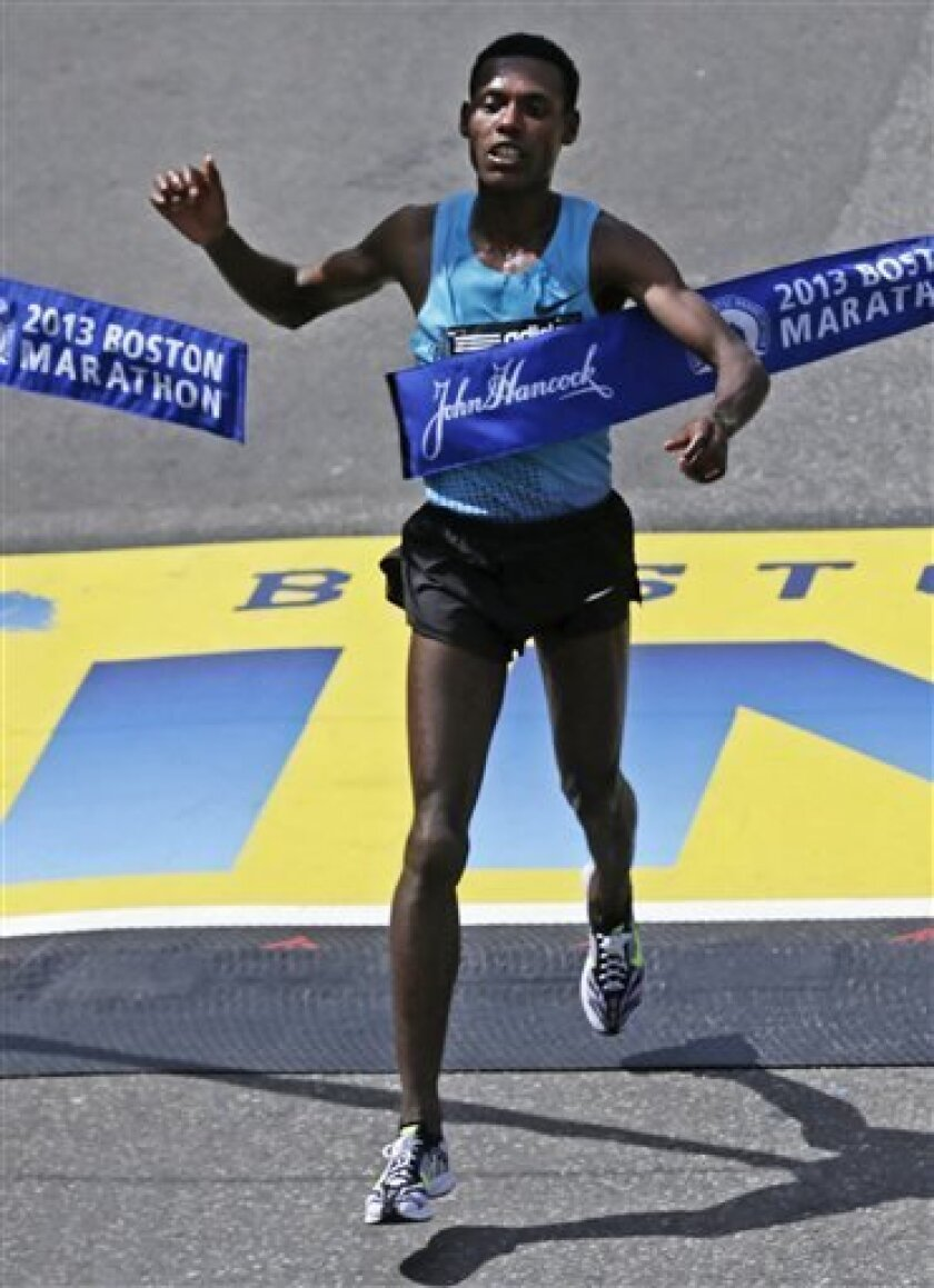Lelisa Desisa, of Ethiopia, breaks the finish line tape to win the 2013 running of the Boston Marathon in Boston, Monday, April 15, 2013. (AP Photo/Charles Krupa)