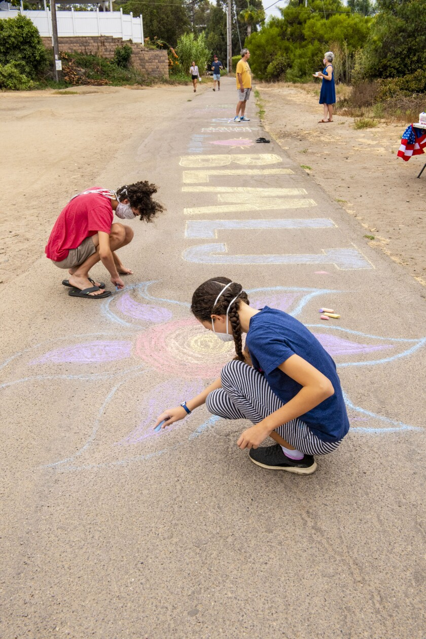 People contribute chalk art during a community Labor Day event to support the Black Lives Matter movement.