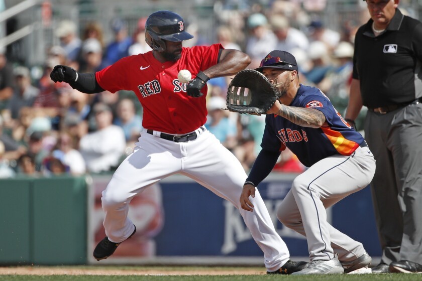 Boston Red Sox's Jackie Bradley Jr. gets back to first safely on a pickoff attempt to Houston Astros first baseman Nick Tanielu during a spring training baseball game, Thursday, March 5, 2020, in Fort Myers, Fla. (AP Photo/Elise Amendola)