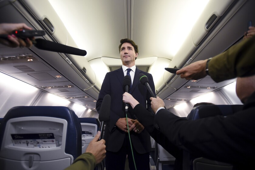 """Canadian Prime Minister and Liberal Party leader Justin Trudeau makes a statement in regards to a photo coming to light of himself from 2001, wearing """"brownface,"""" during a scrum on his campaign plane in Halifax, Nova Scotia, Wednesday, Sept. 18, 2019. (Sean Kilpatrick/The Canadian Press via AP)"""