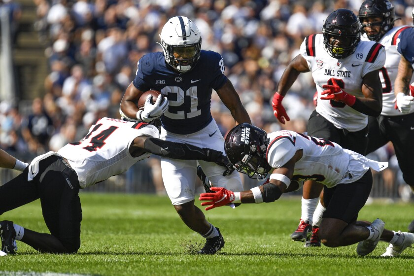 Penn State running back Noah Cain (21) splits two Ball State defenders on a first half run during an NCAA college football game in State College, Pa., on Saturday, Sept. 11, 2021. Penn State defeated Ball State 44-13. (AP Photo/Barry Reeger)
