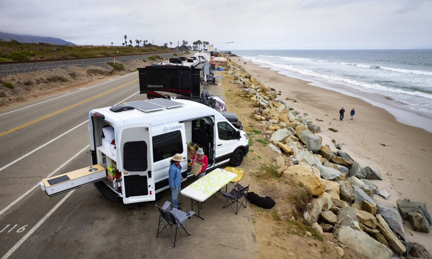 A couple set up a table and chairs next to a van along the beach