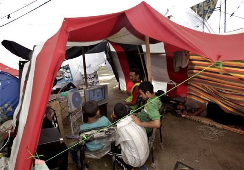 Egyptian protesters watch television inside their tent, with Egyptian flag colors, during their protest in Tahrir Square in Cairo, Egypt, Tuesday, July 12, 2011. Thousands of Egyptians have braved scorching summer heat to hold one of their biggest protests in months, filling streets in Cairo and other cities to demand trials for members of Hosni Mubarak's regime and express frustration with the slow pace of change. (AP Photo/Khalil Hamra)