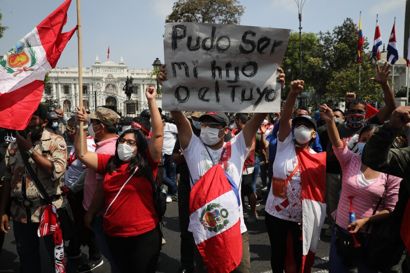 """Standing amid other protesters, a man holds a sign reading in Spanish """"It could have been my son or yours."""""""