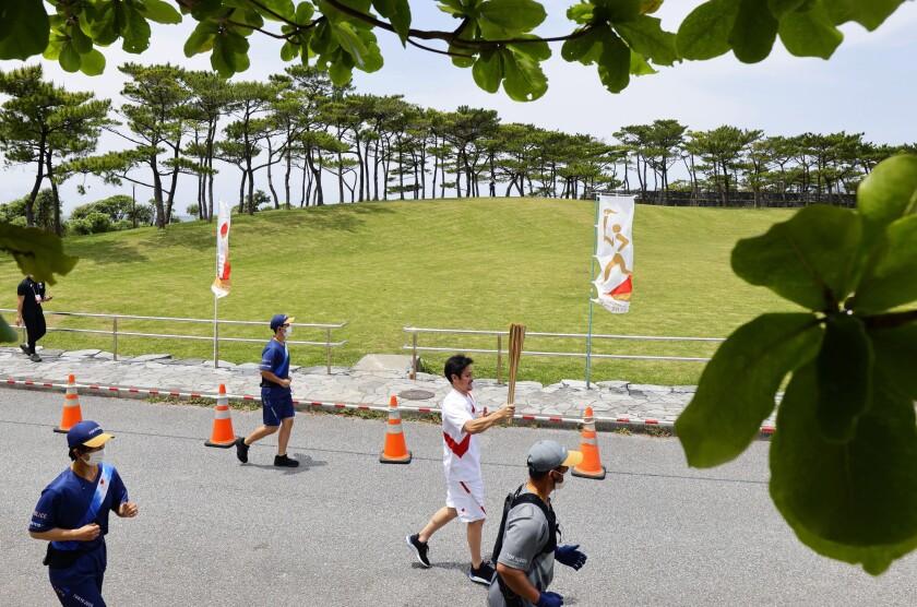 Un corredor relevista lleva la antorcha olímpica en Nago, prefectura de Okinawa, Japón, sábado 1