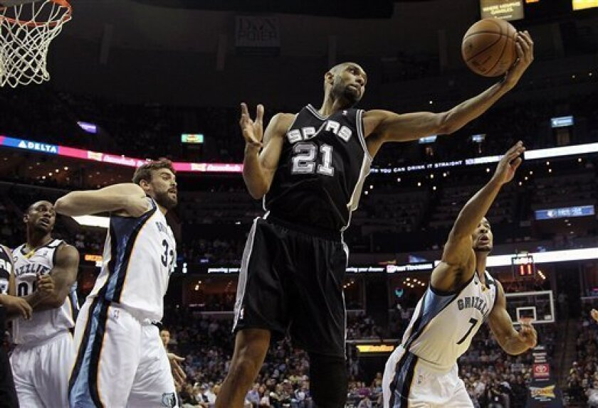 San Antonio Spurs forward Tim Duncan (21) grabs a rebound against Memphis Grizzlies defenders Darrell Arthur (00), Marc Gasol (33), of Spain, and Jerryd Bayless (7) in the first half of an NBA basketball game on Friday, Jan. 11, 2013, in Memphis, Tenn. (AP Photo/Lance Murphey)
