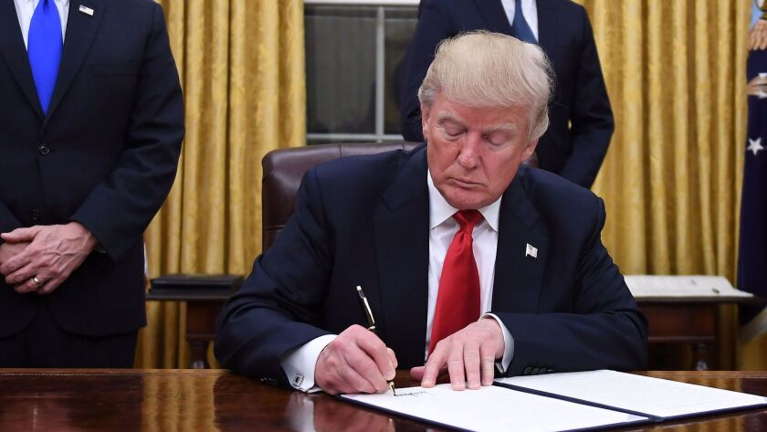 President Donald Trump signing his executive order undermining the Affordable Care Act on Jan. 20.