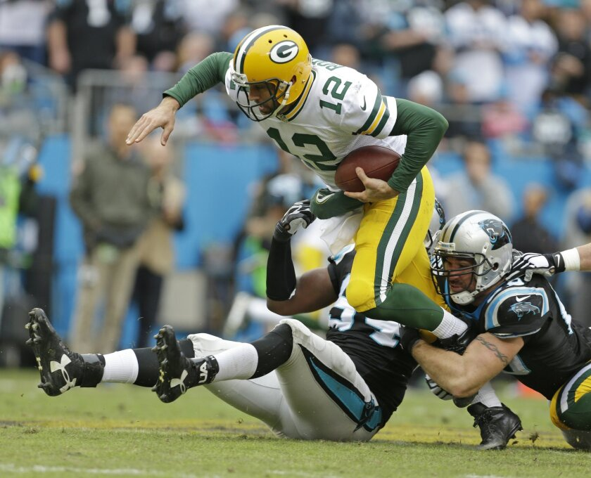 Green Bay Packers' Aaron Rodgers (12) is sacked by Carolina Panthers' Kony Ealy (94) and Jared Allen (69) in the second half of an NFL football game in Charlotte, N.C., Sunday, Nov. 8, 2015. (AP Photo/Bob Leverone)