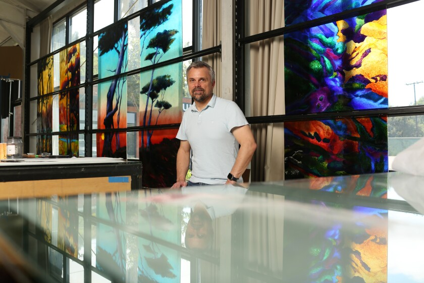 David Judson in front of fused-glass landscapes in his company's studio.