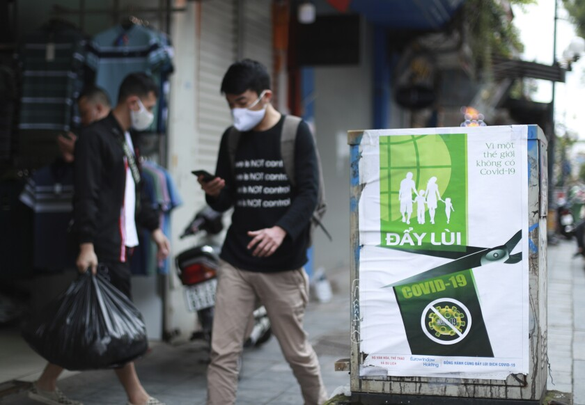"A poster in Hanoi reads ""Fighting COVID-19,"" in Vietnamese. Many business activities resumed Thursday as Vietnam lifted a nationwide lockdown to contain the spread of COVID-19."