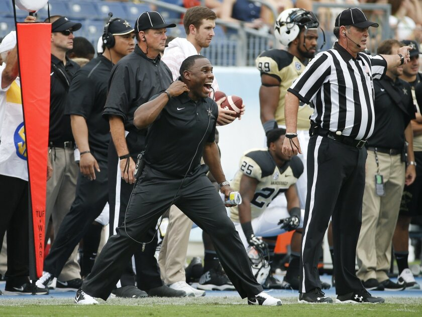Vanderbilt head coach Derek Mason, center, yells to his players in the first quarter of an NCAA college football game against Mississippi, Saturday, Sept. 6, 2014, in Nashville, Tenn. (AP Photo/Mark Humphrey)